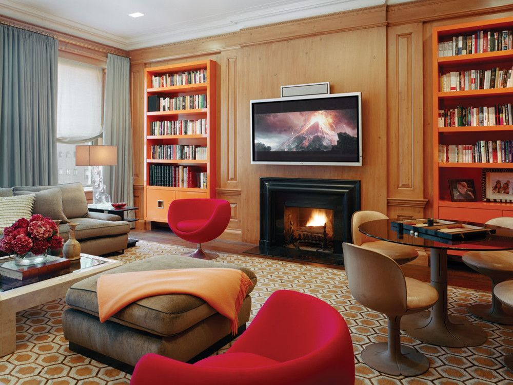 Designer Joe Nahem retained original millwork, but stripped and limed it, then added a David Hicks-style hand-knotted carpet from Beauvais, bookshelves in Hermès orange lacquer, and a 1970s Pierre Paulin games table and chairs originally made for the Élysée Palace.