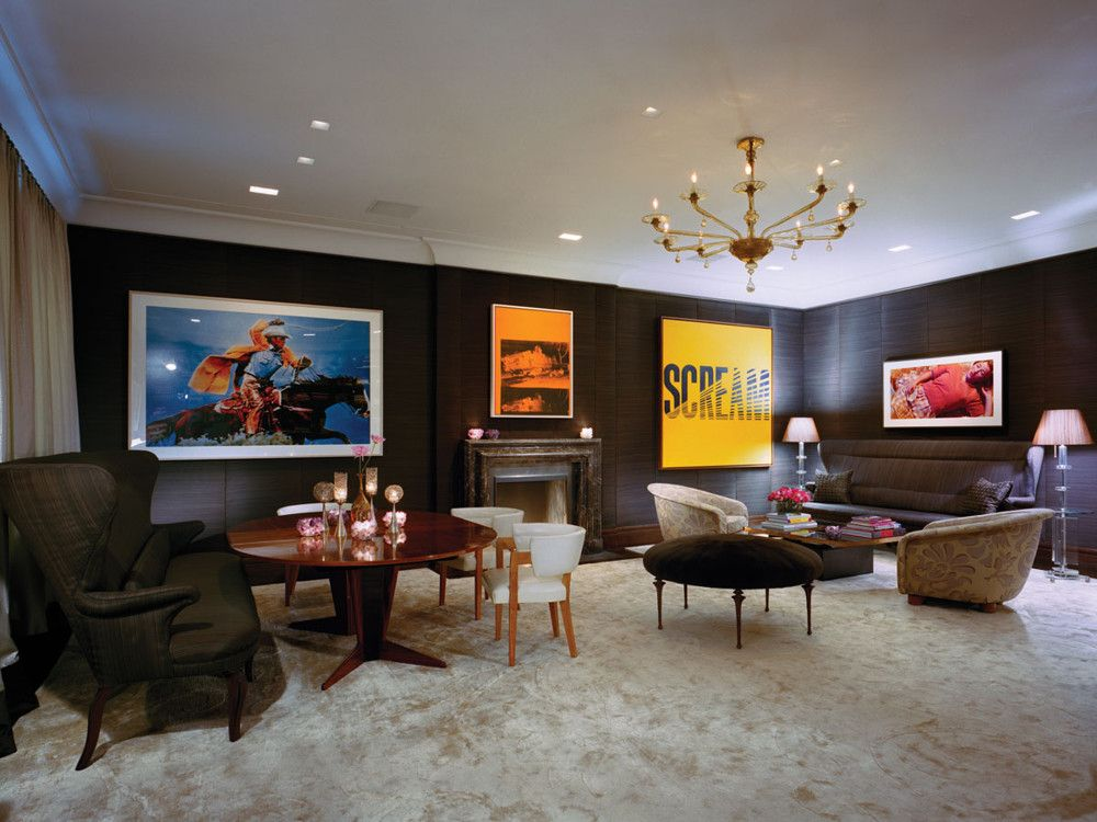 Forget tame family portraits. This dining room boasts challenging works by (left to right) Richard Prince, Andy Warhol, Prince again, and Cindy Sherman. A Chesney's marble fireplace separates the dining area's Jacques Quinet table and Eugene Schoen chairs from the seating area's Royère lounge chairs. Custom horsehair banquettes flank the space, matching the horsehair walls.
