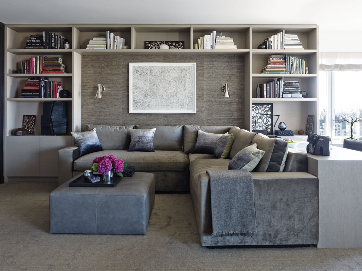 "The family room, done in taupe neutrals, is ""the most comfortable room in the house,"" according to Daria Schrage. Charcoal grasscloth by Donghia lines the alcove, and the custom sectional by Furniture Masters is upholstered in grey velvet by Fabricut."