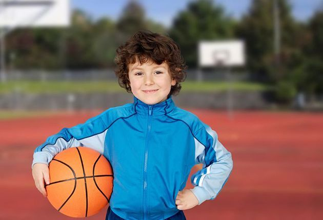 young boy with basketball on court