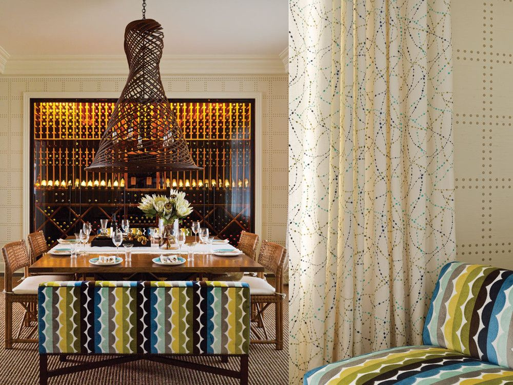 Left: The dining room, a perfect square, is home to the husband's special wine wall. The Roche Bobois dining table is illuminated with a crafted wood pendant from Coup D'Etat. Boldly patterned fabric by Jonathan Adler covers the custom benches. A simple sisal rug grounds the design. Right: The dining room walls are covered with Rivet wallpaper from Phillip Jeffries.