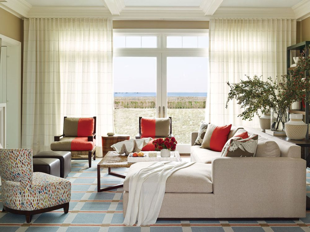 The living room is designed for both entertaining and cosseting. Robinson and Lipner created a capacious sectional sofa and had it upholstered in an outdoor-grade fabric from Rogers & Goffigon. The rush coffee table, a custom design from Room, adds a casual note. The side chairs, also rush, are by A. Rudin, but the lively two-tone pillows atop them were created by the duo from Sunbrella. The house's crisp geometric proportions inspired the designers to play off them. The loose-weave linen curtains from Lulu DK have a subtle windowpane check; the custom-woven and custom-colored rug, which Stark Carpet produced, plays with lines and squares.