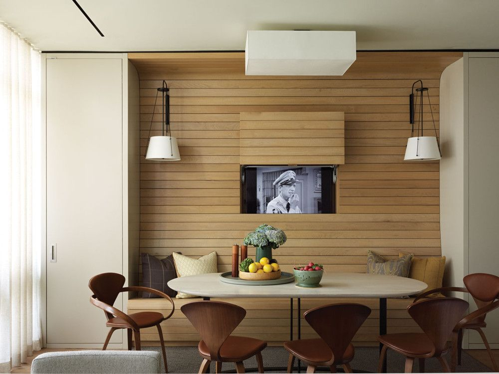 "The kitchen centers on a built-in breakfast nook with a wall of bleached walnut paneling that seamlessly incorporates a bench and a pocket for a flat-screened TV. Architect Ben Herzog says Dumais did a full-scale mock-up for the clients so they could adjust the seating for greatest comfort. ""With 12-foot-long planks of unblemished walnut,"" Herzog adds, ""it took a while to source the wood."""