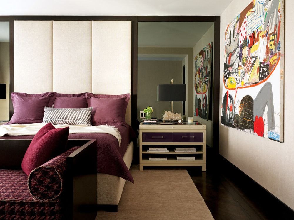 To cater to the wife's love of deep purple, Delrose had extra-wide, lacquered night tables made in contrasting shades of cream and eggplant with Lucite pulls. An elongated headboard upholstered in a linen from Romo and smoked glass mirrors on either side of the bed enlarge the room and add a dramatic flair. A silk carpet and a Calvin Klein chaise keep the restful vibe intact. Painting by Eddie Martinez.
