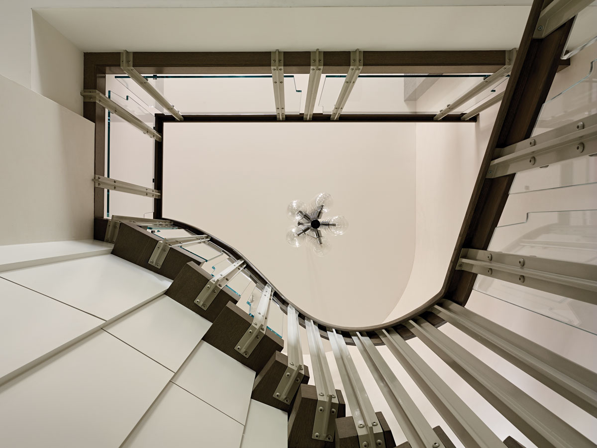 The dramatic staircase is framed with custom glass and aluminum panels, an homage to Fontana Arte.