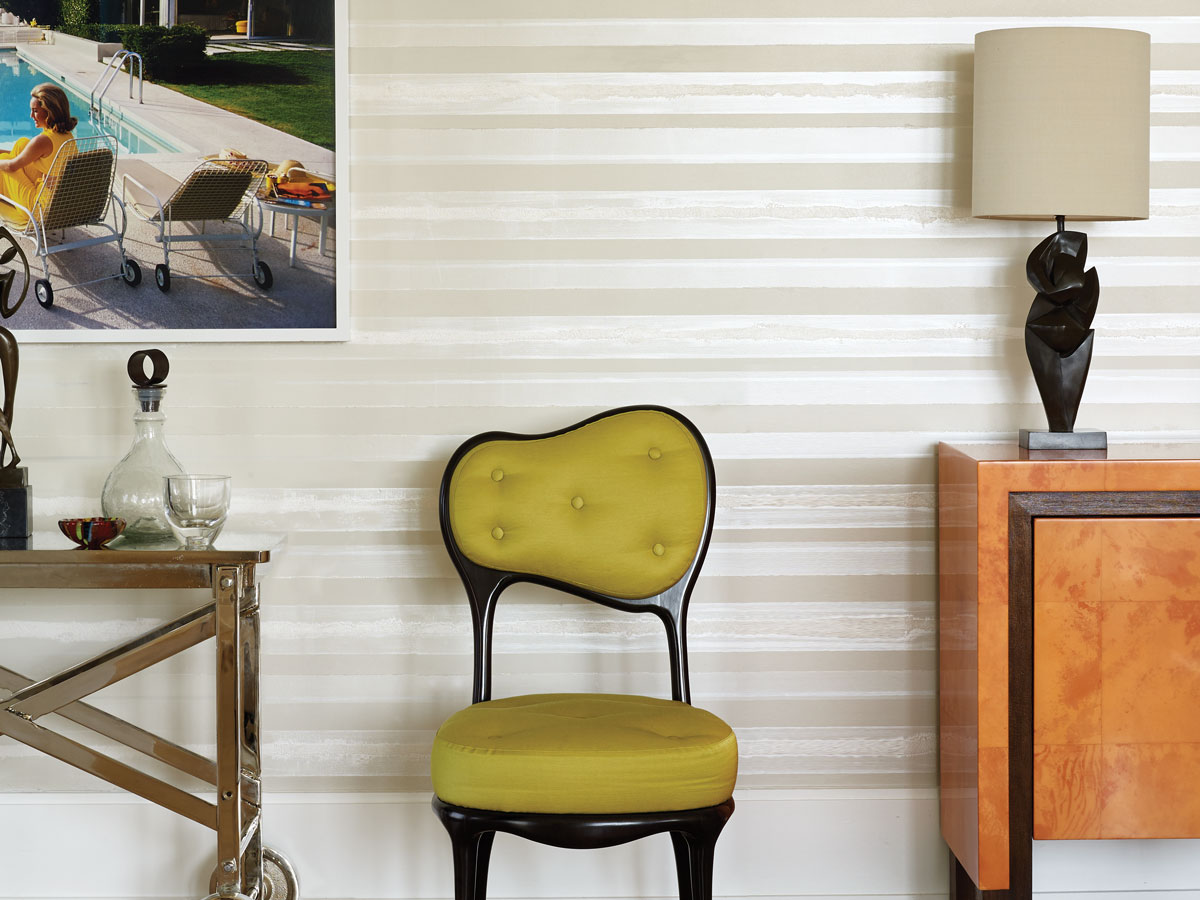 "A Mario Bonetti ""Iris and Poppy"" chair in acid green Dedar fabric adds an electric jolt of color in the neutral room. A Porta Romana lamp, ""Danseur,"" provides sculptural interest on the Red Cloud credenza by Lorin Marsh."