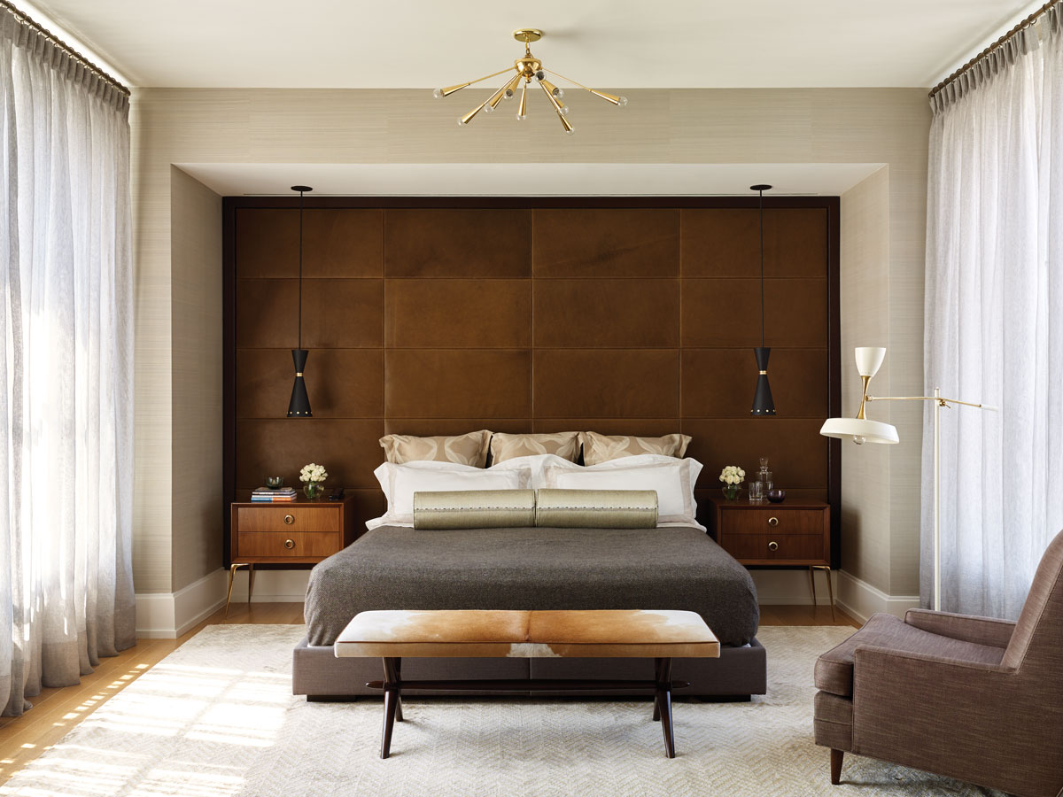 In the master bedroom, the custom platform bed is upholstered in fabric from Pierre Frey. The panel wall, wrapped in leather from Jerry Pair, functions as a massive headboard. A Robsjohn-Gibbings bench and a vintage floor lamp add a midcentury feel to the room.