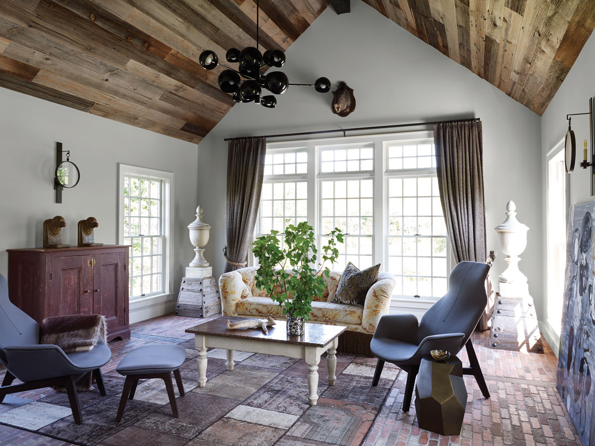 In the den/TV room, the wood ceiling is reclaimed from a Pennsylvania barn. Other gutsy elements include a brick floor, an antique copper-topped table, and oversized antique finials.