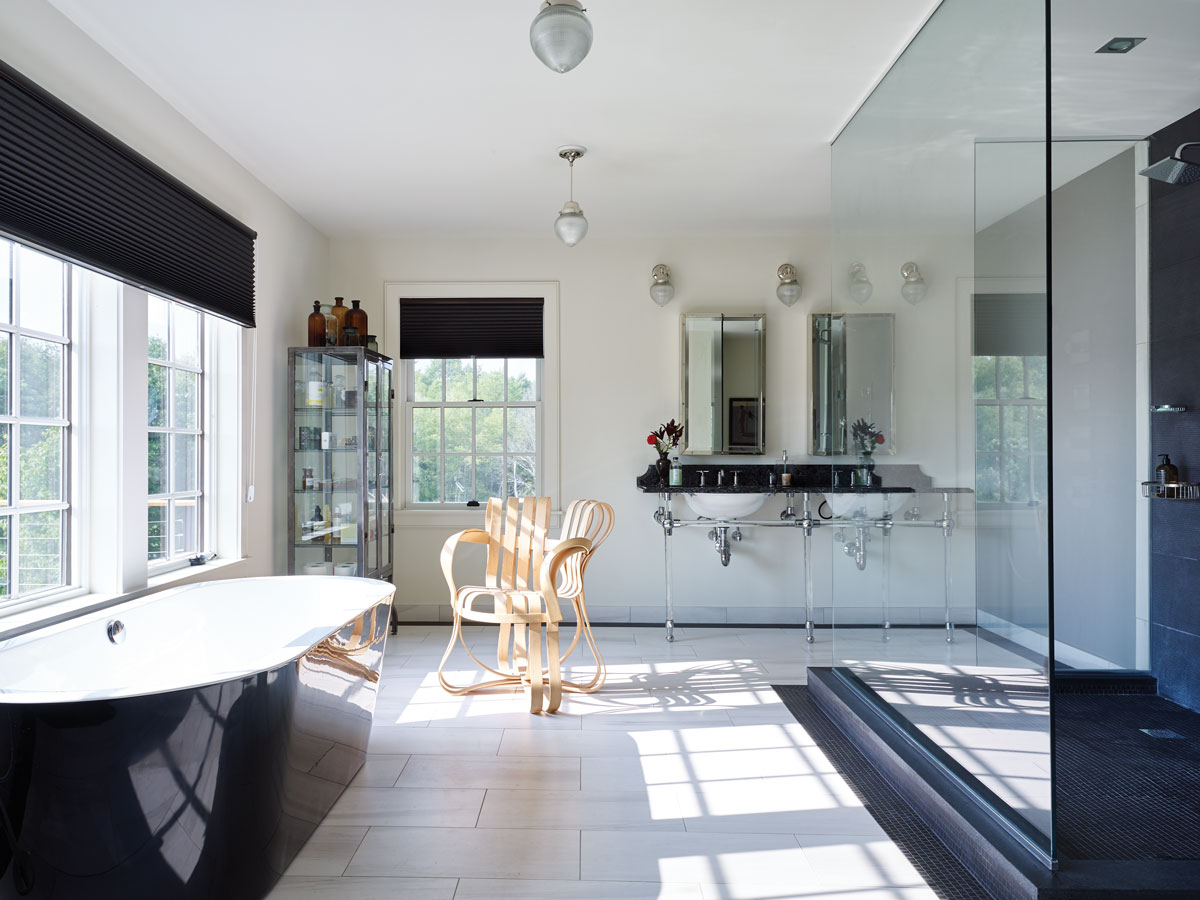 In the master bath, a black and white palette takes over; the tub from Signature Hardware puts the bather practically in the landscape; a shower built for two overlooks the lake.