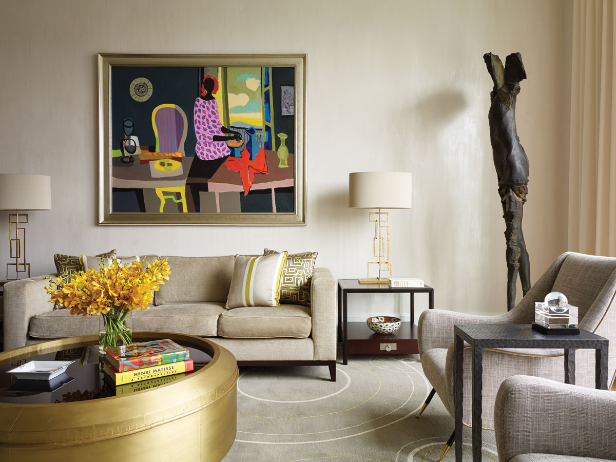 A round, brass-and-glass coffee table from Bernhardt echoes the custom designed Jarvisstudio rug. Sculptural table lamps from Porta Romana sit on vintage midcentury end tables by Michael Taylor. Over the sofa, a painting by Marcel Mouly adds graphic interest and pops of color, while a bronze sculpture by Stephen De Staebler fills the corner. The custom plaster wall finish by David Gardiner from Field Decorative Finishes envelops the room in subtle glamour.