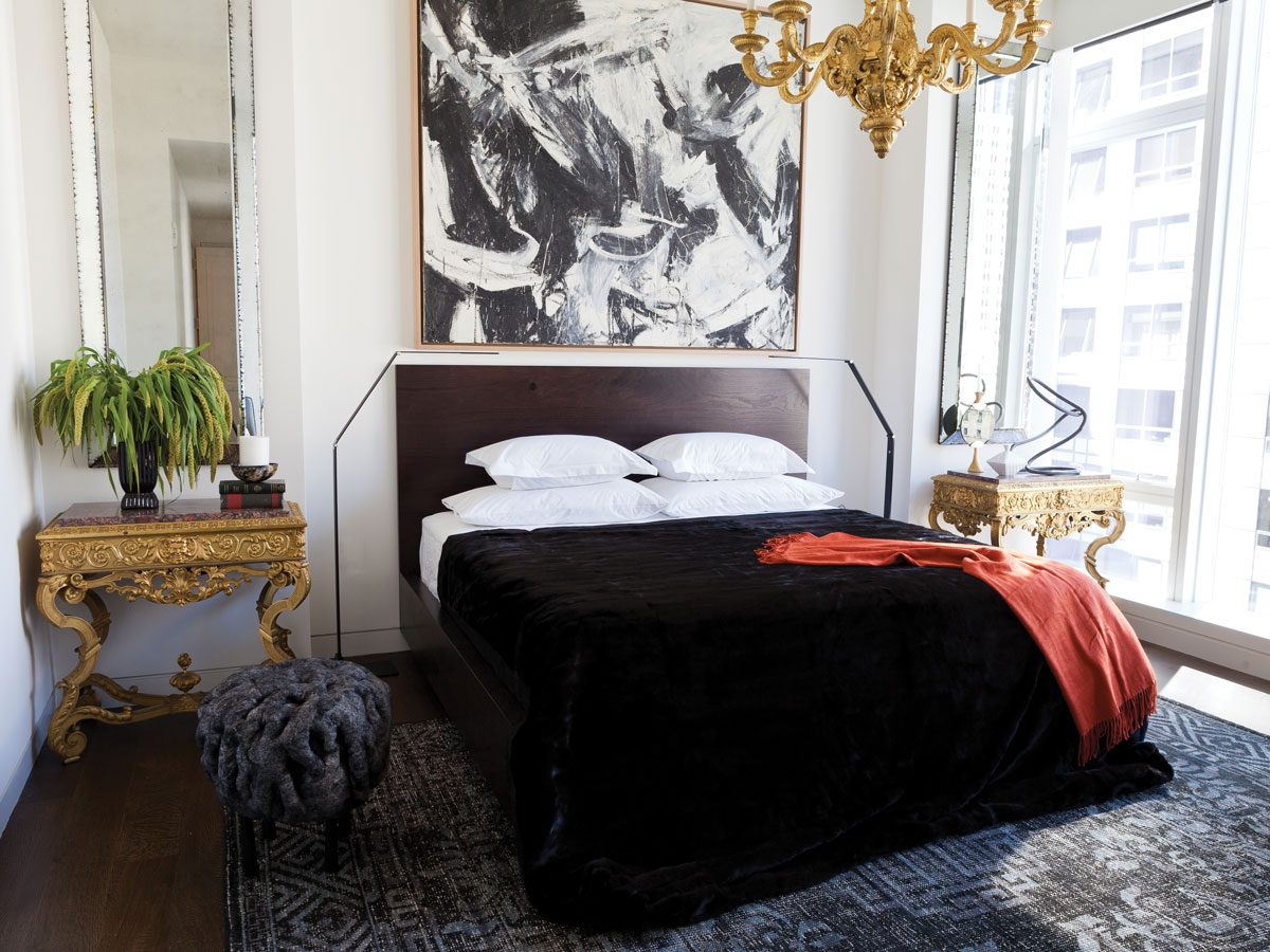 In the master bedroom, the designer played up the 12-foot-ceilings with symmetrically placed mirrors designed to exaggerate. A wool-and-silk stool from Maison Gerard mimics the movement of the Nicolas Carone painting above the bed.