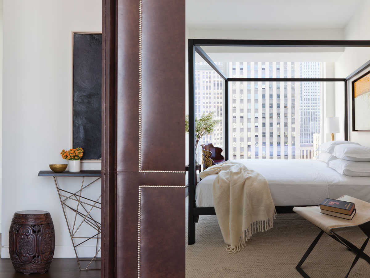 Left: To cater to the client's love of more compartmentalized spaces, Anderson added leather doors with nailhead details to separate the living space from the entry gallery. Right: Neutral tones and an open canopy bed elevate the guest bedroom's light ambiance. A barrel-shaped French Empire chair recalls the vernacular of the rest of the home.