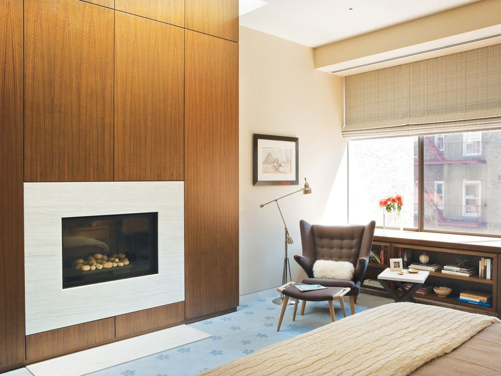 With 12-foot ceilings, the fifth floor master bedroom is light-filled and spacious. Set flush into the walnut-paneled wall opposite the bed is the fireplace's Stellar white stone surround.