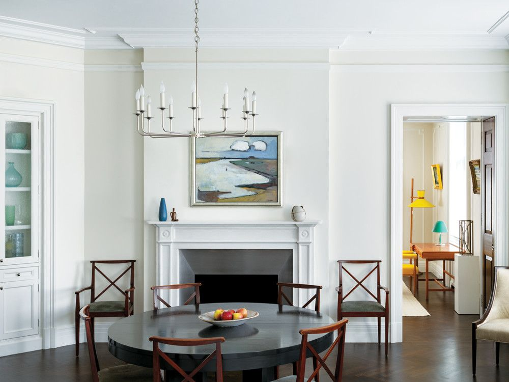 The kitchen opens to the adjacent dining room, where the architects selected the Antoine Proulx table and chandelier. Redone fireplaces throughout with new mantels and surrounds were also part of the architect's brief for the renovation.