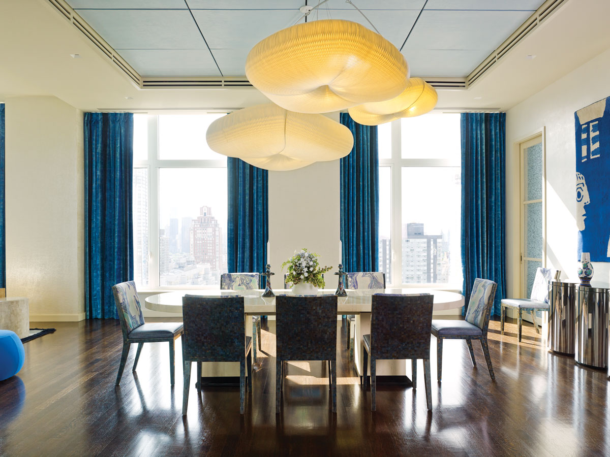 Designers Guild blue velvet drapes emphasize the 14-foot ceilings and refer to East River water views. The Molo Design accordian paper pendants simulate clouds. A bespoke lacquered shagreen table is wreathed with custom dining chairs made in Bali. The latter feature abalone backs and Sabina Fay Braxton fabric on the front.