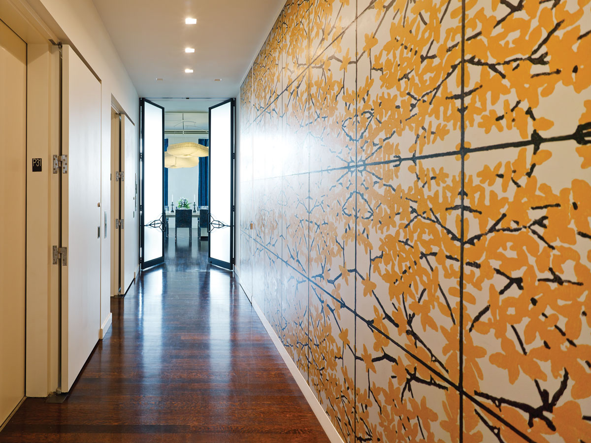 The Richard Woods mural in the elevator lobby incorporates a golden palette; In another corner of the den, an Eames lounge chair and a 1970s limestone table by Michael Taylor.