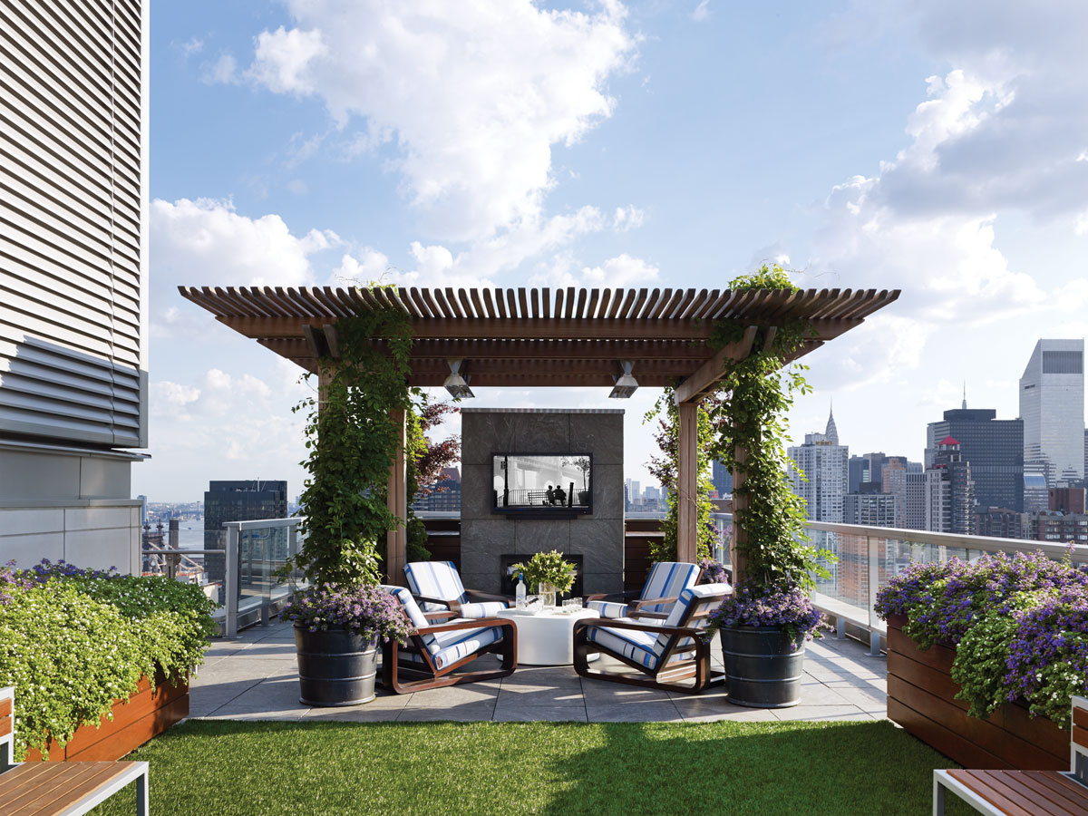 Architect Edward Siegel removed pavers on the 2,850-square-foot roof terrace to lay in grass and built a pergola over the fireplace. Custom teak seating is based on a Royère design.