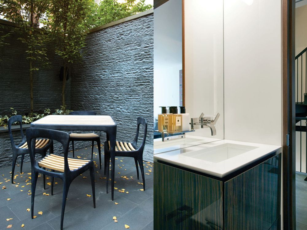 "Left: A Henry Hall ""Flow"" collection table and chairs in the redesigned back garden. Right: A powder room vanity repeats the modern theme."