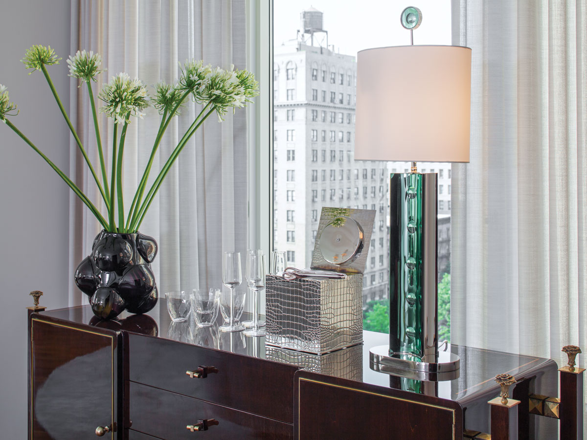 In the living room, a green glass lamp from Lorin Marsh by Roberto Rida sits on a midcentury walnut sideboard by Albano. A custom rug by Fort Street Studio sits underfoot.