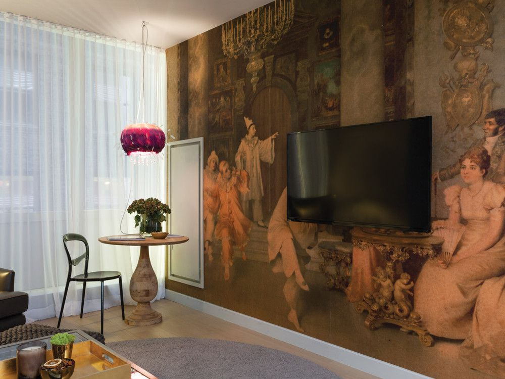 Noriega-Ortiz turned the focus of the living room inward with a wallpaper mural created and installed by Infinity Pix from an original painting by Francesco Beda, which he found at a flea market.