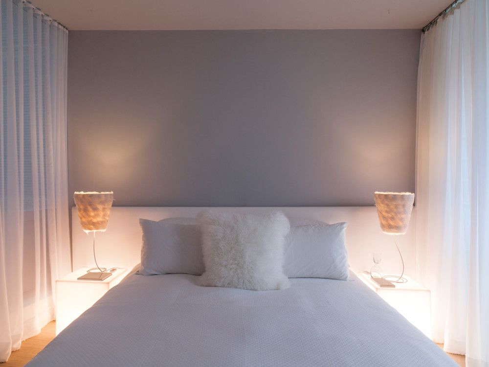 In the same apartment's master bedroom, sheer draperies in chiffon from Rosebrand envelope the bed romantically. The feather lamps are from ABYU Lighting.