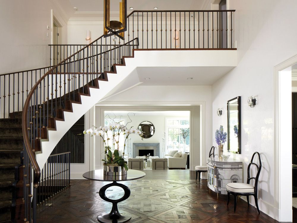 In the entry hall, a rail from Koenig Iron Works adds filigree to the stair; a floor of reclaimed parquet de Versailles offsets Venetian plaster walls. Artful notes include a Fornasetti chest and a Herve Van der Straeten chandelier from Maison Gerard.