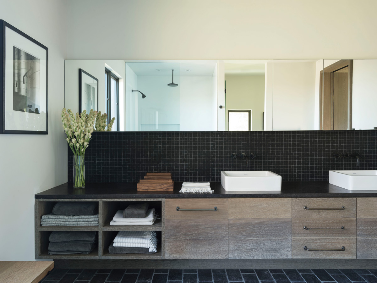 The backsplash behind the sink is made of a mosaic of matte black glass tiles.
