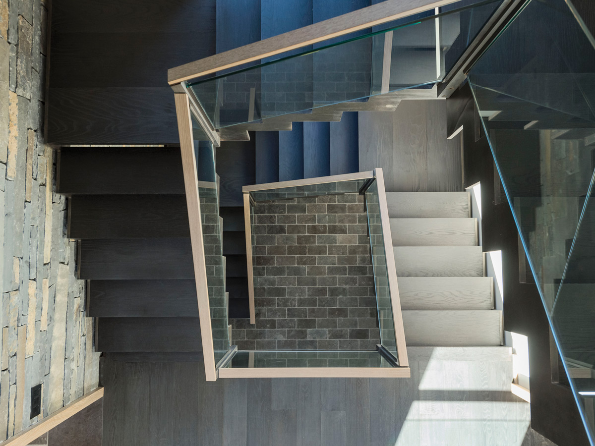 The staircase of black rolled steel divides the glass pavilion from the barnlike wing.