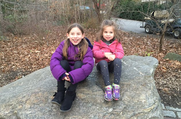 young girls sitting on a rock