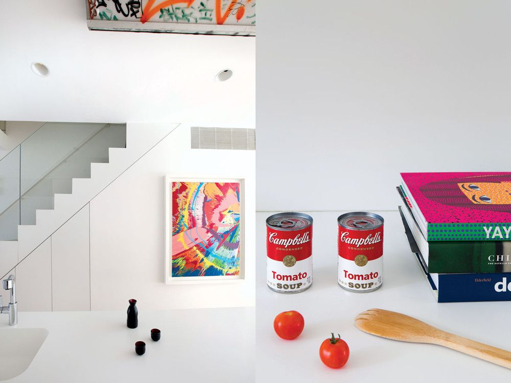 Left: The explosive energy and color of a Damien Hirst painting is counterbalanced by the geometry of the staircase and the understated elegance of an antique sake set. Right: A kitchen tableau invokes Warhol next to exhibition catalogues on de Kooning, Kusama, and Chinese contemporary art.