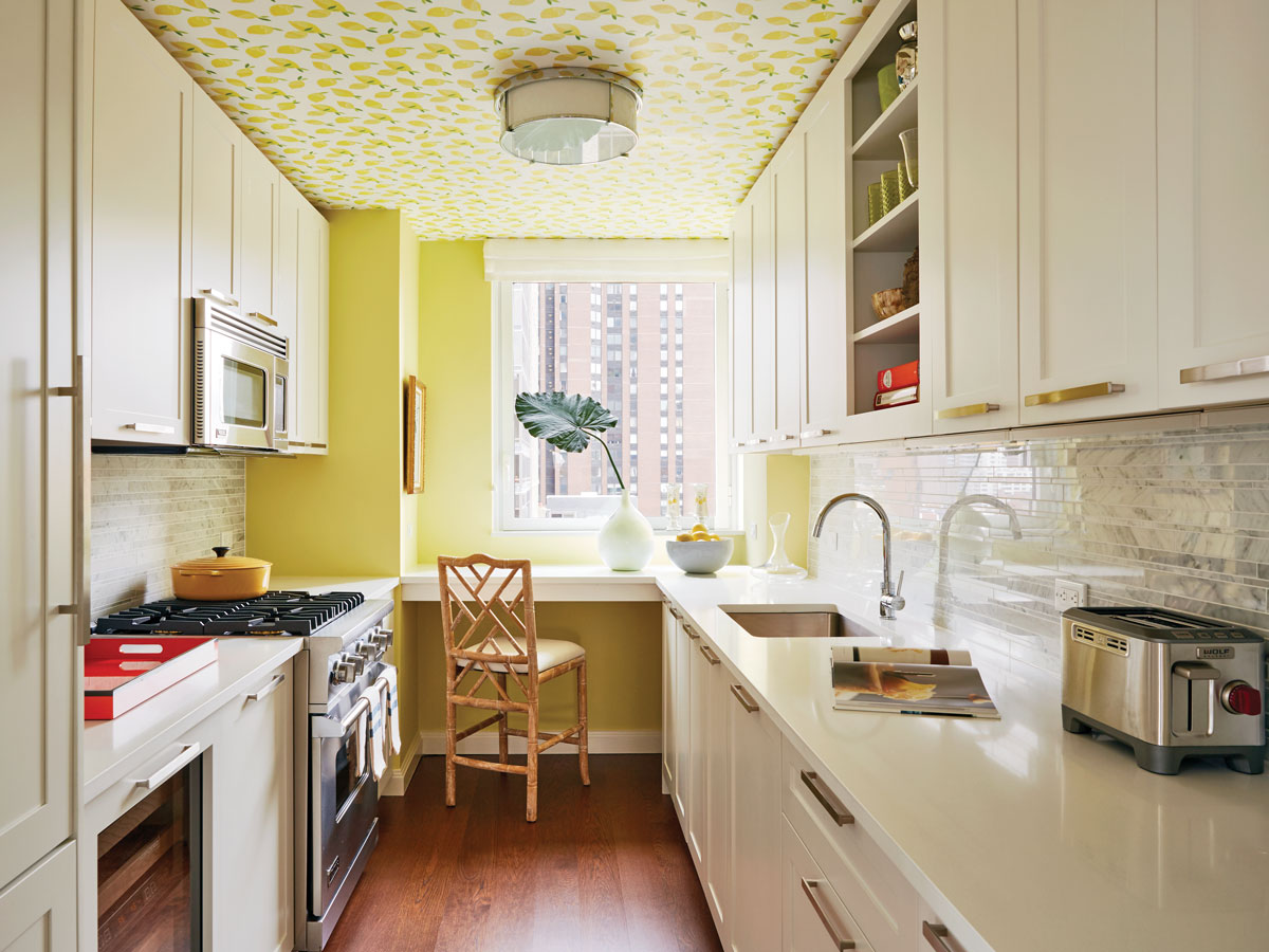 The bright yellow kitchen with Serena & Lily Lemons wallpaper on the ceiling.
