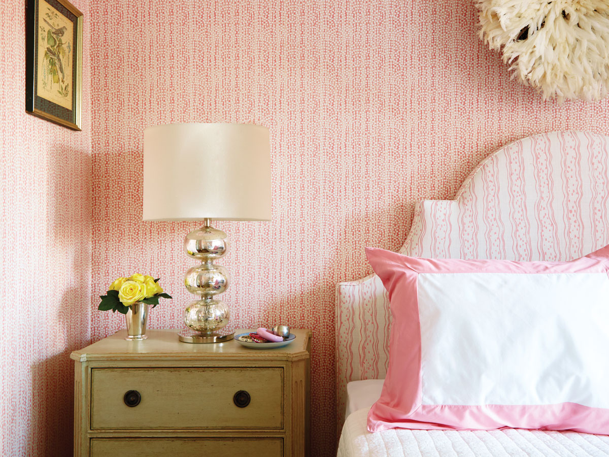 The girl's bedroom is pretty in pink. Savannah stripe by Christopher Maya covers the headboard. The desk, chair, and side table are from Chelsea Editions.