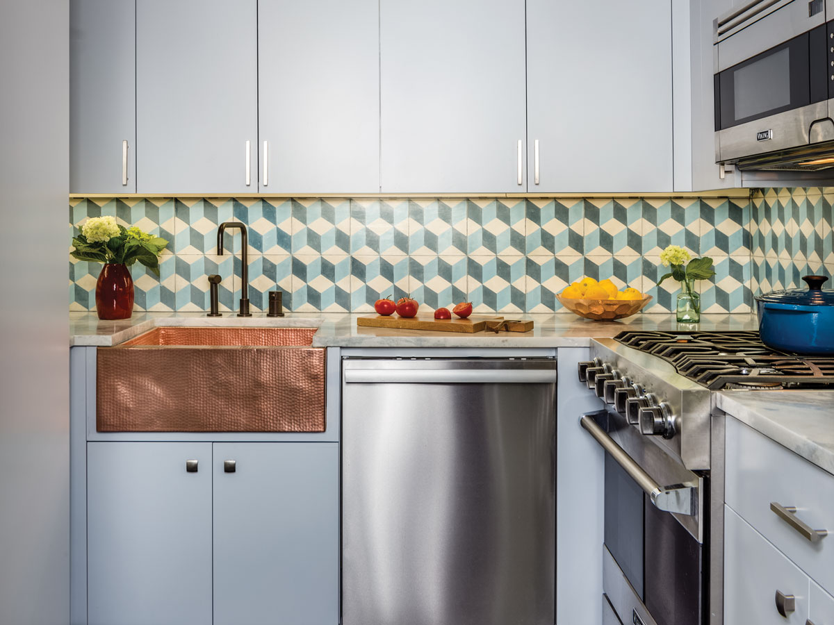 The kitchen is the most subdued room in the home, with geometrical tiles from Amethyst Artisan, a blue Damascus marble countertop, and the warmth of a hand-hammered copper sink