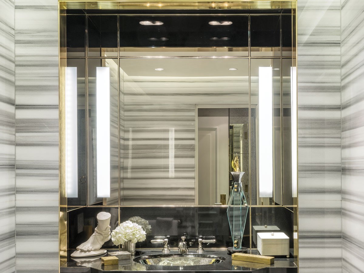 A niche in the bathroom lined with zebrino marble and accents of black marble set into a bronze frame.