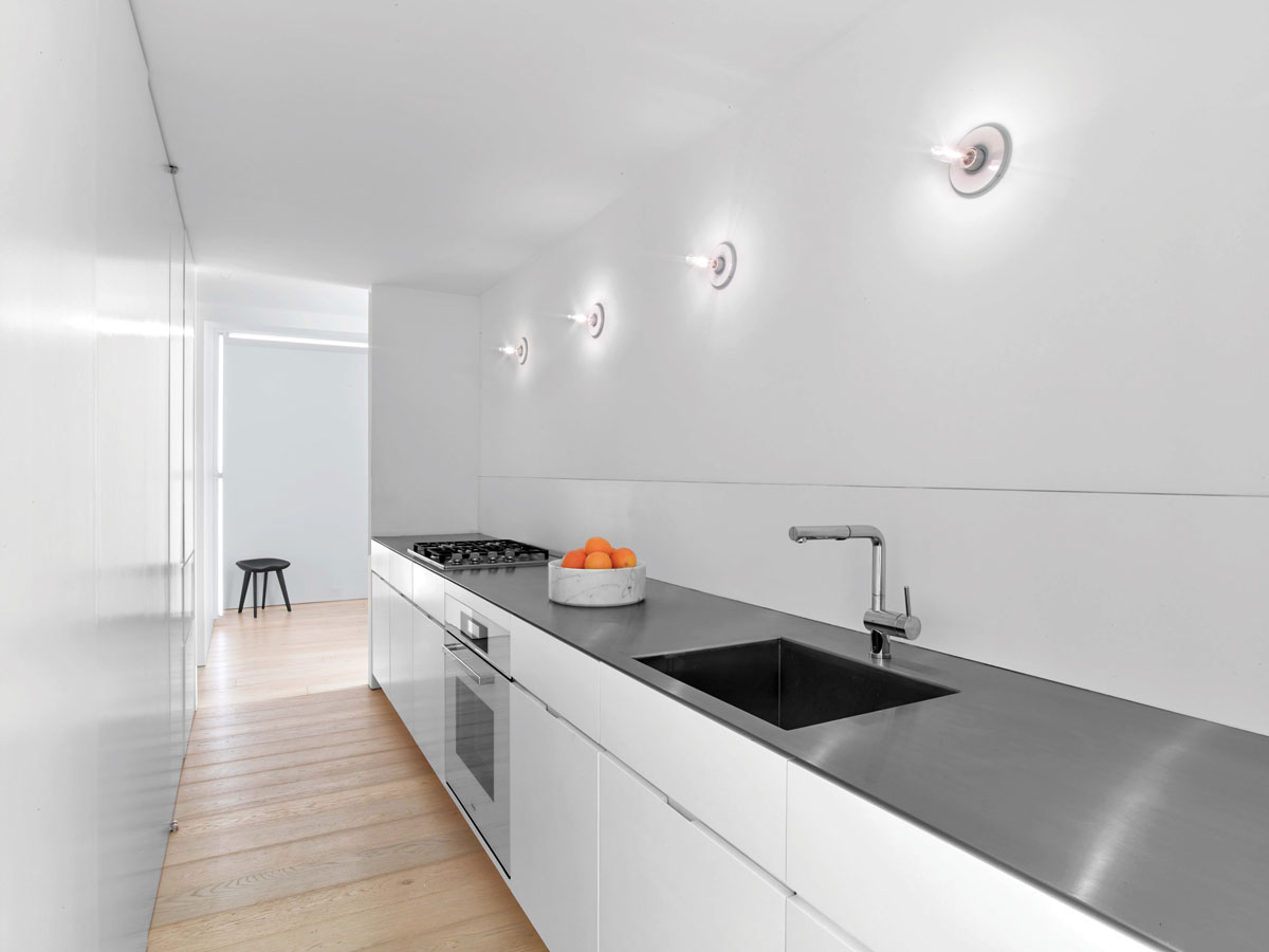 While keeping the kitchen's galley layout, the designers updated one side with a brushed, stainless-steel countertop, a recessed Corian backsplash, and exposed lighting. On the facing side they avoided the messy perils of exposed shelving and created cabinetry for storage and more, including a Sub-Zero refrigerator.