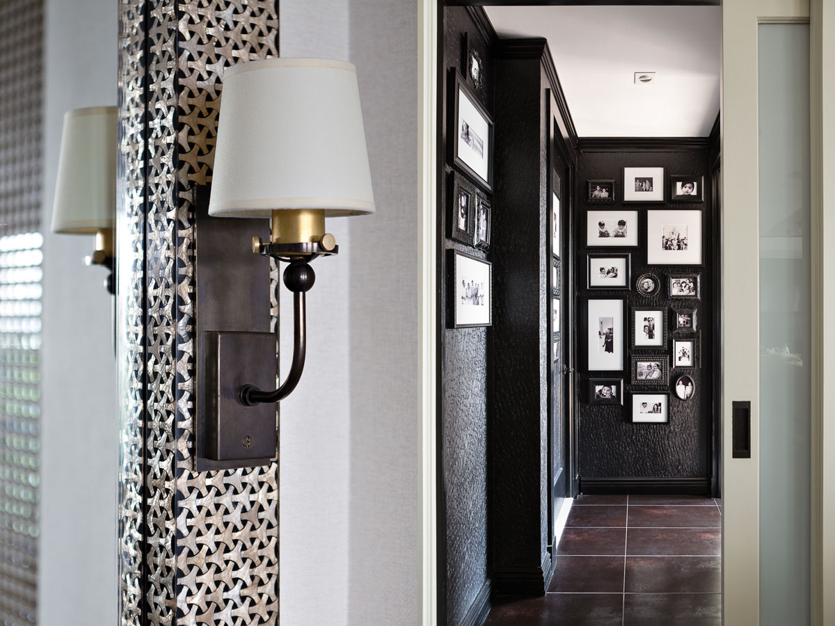 Left: The sconce from O'Lampia is attached to the shell-encrusted mirror over the banquette. Right: The hallway leading to the guest suite is covered in black vinyl wallpaper from Sonia's Place and lined with family photos. The back wall is actually a door to a coat closet. Rusted silver tiles on the floor are from Nemo.