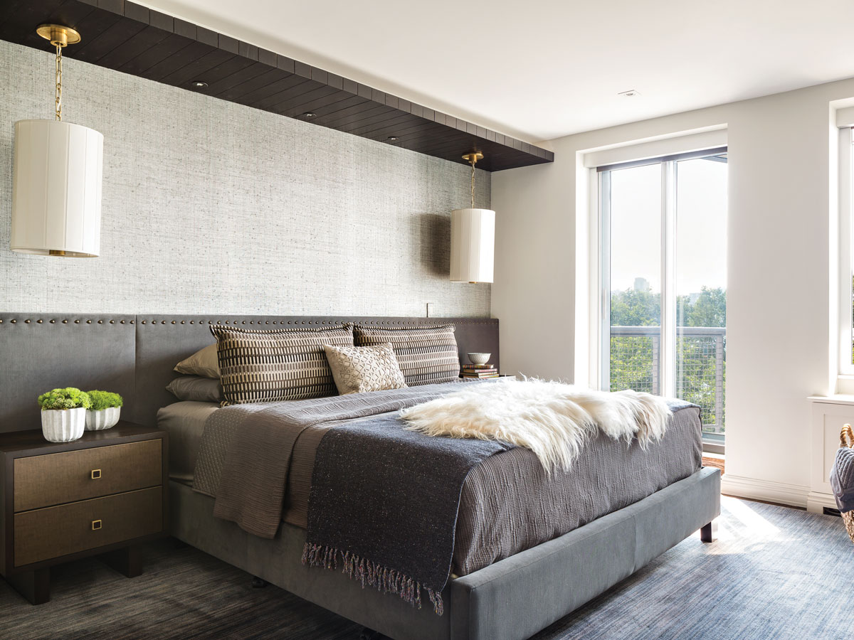 A grey velvet bed from Jensen-Lewis takes center stage in the master bedroom. Stuart got yards of extra fabric to cover the wall behind it. A wood plank overhead spans the room's length. The pendants are from Visual Comfort.