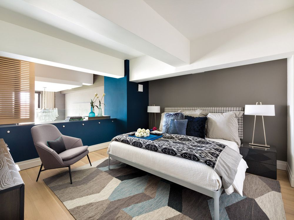 In the guest bedroom, a felt roller shade, which is installed above the opening overlooking the living room, acts as a sound buffer. The space is simply furnished with a bed and end tables from Design Within Reach, a dresser from Blu Dot, and a rug from West Elm.