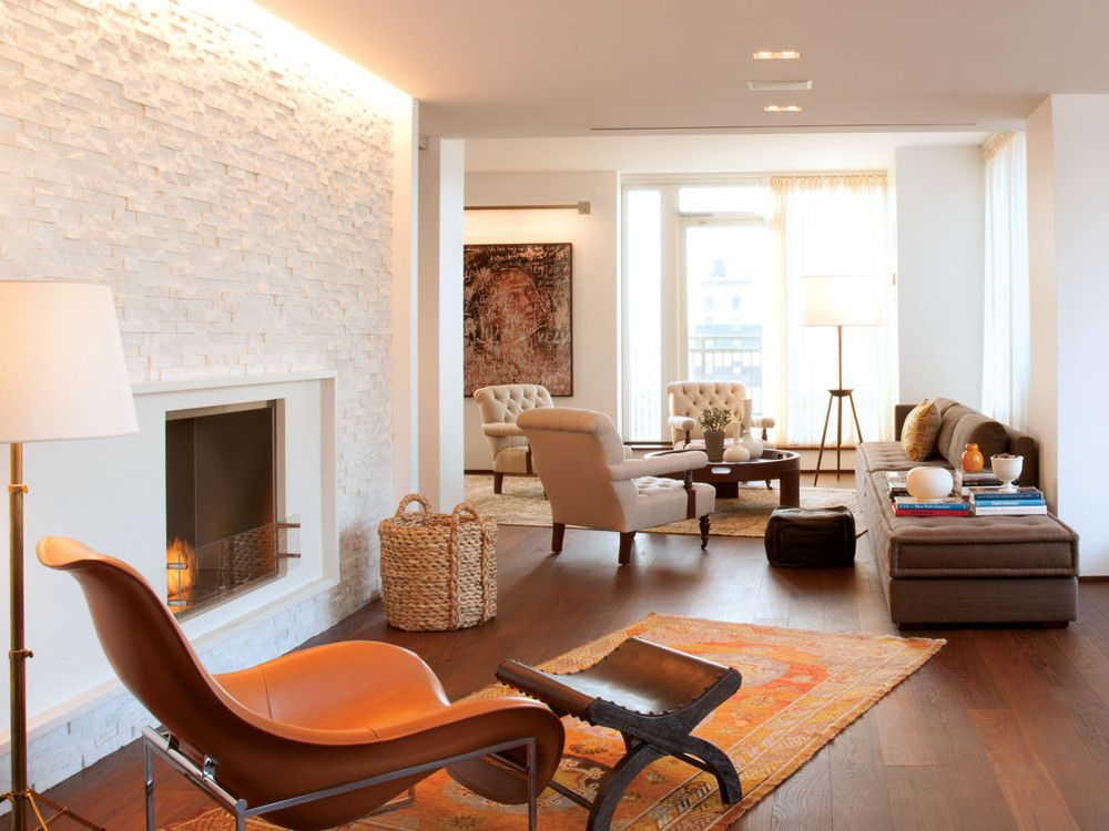 In Bhalla's L-shaped living room, McIntosh housed a fireplace from Heat & Glo Fireplaces in a custom surround amid a feature wall of stacked marble chunks. A lounge chair from B&B Italia, a vintage ottoman, and a standing lamp from Aero create a cozy spot for reading. Two vintage Samarkands from Doris Leslie Blau define the seating areas and make reference to the Silk Route. McIntosh designed the custom tufted club chairs based on a classic English model, and used a custom tufted sectional to bridges the two areas.