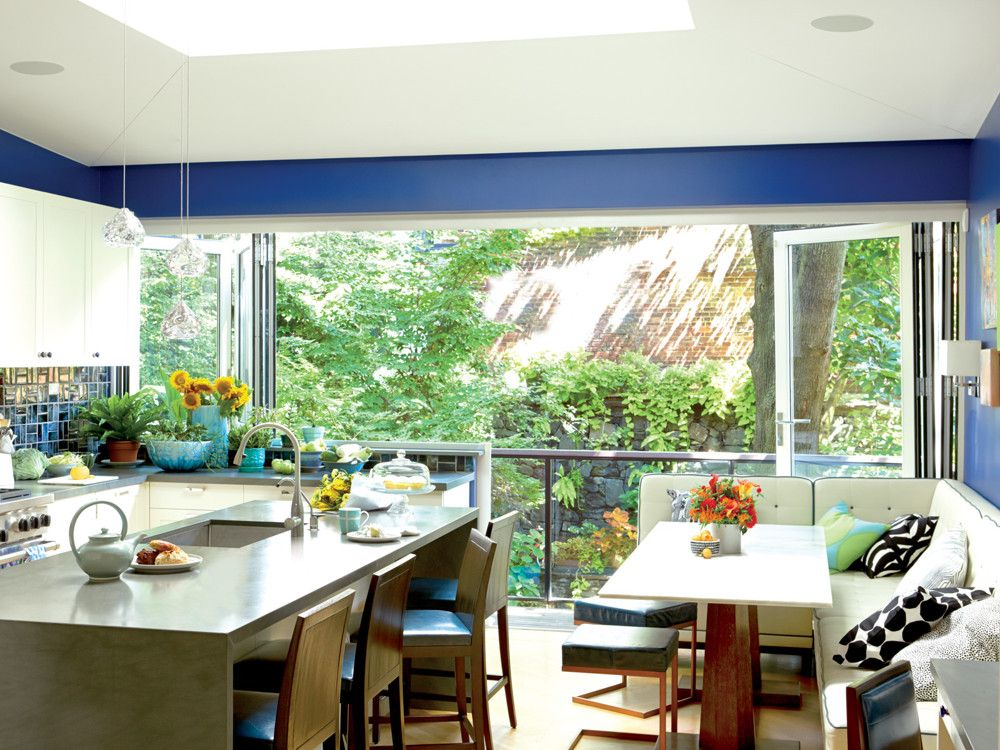 The NanaWall system allows the family to leave the kitchen and breakfast nook open to the deck and the outdoors. The kitchen's Bluestone countertop plays off the hand-made, hand-glazed, iridescent backsplash tiles from Fired Earth. The banquette and Carrara marble table top are custom by Hamilton Design Associates.