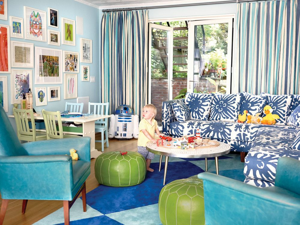 The playroom, or mission control for the children, is on the garden level. A coral-inspired fabric from Quadrille on the sectional plays well with the multi-colored rug and the eye-catching blue leather chairs. Poufs from Serena & Lily. Artwork is the kids' own.