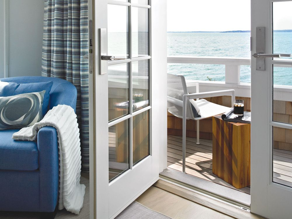 The couple can just step outside the bedroom door to enjoy the sea view from the deck. Curtains made from Kravet fabric provide a screen from the summer sun.
