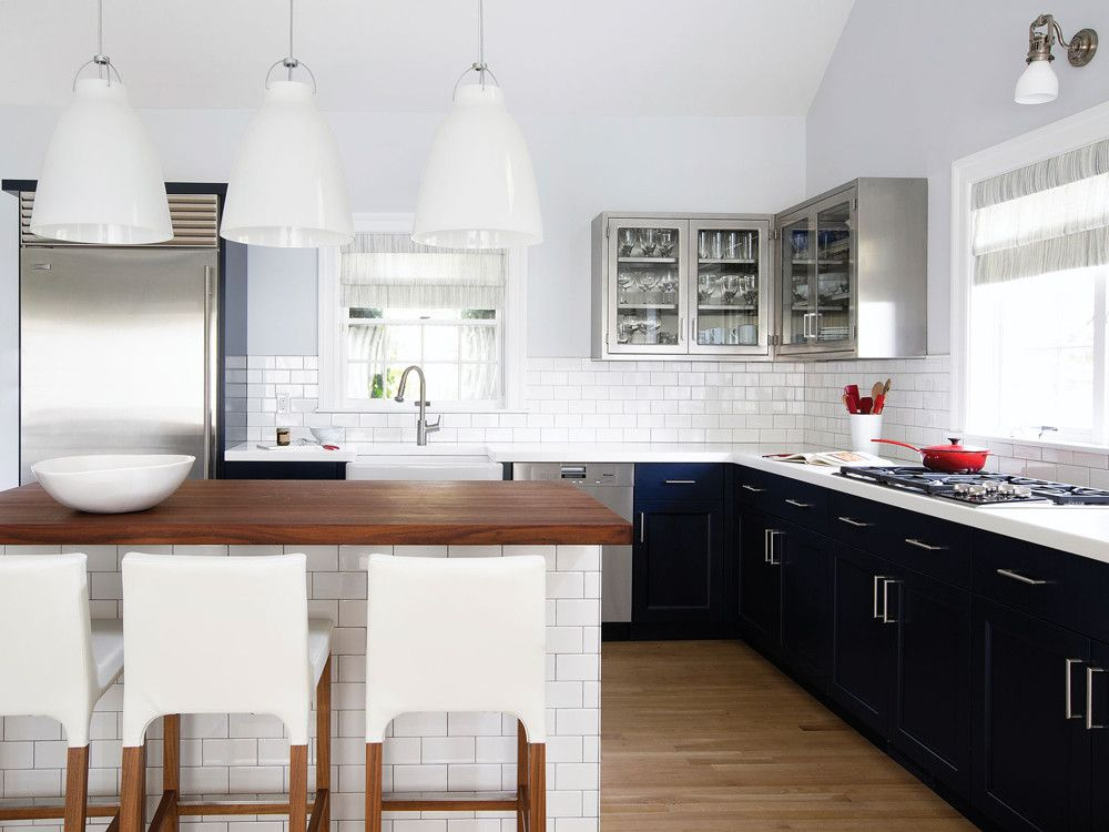 Lower cabinets are lacquered navy blue (good for concealing finger prints); the stainless steel upper cabinets are from Polished Modern; classic subway tiles from Ann Sacks surface the backsplash and island.