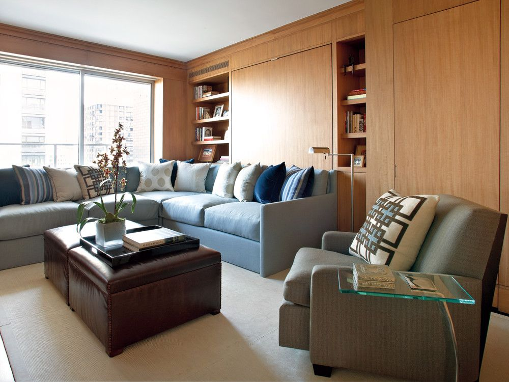 The back of the custom Holland & Sherry wool flannel-covered sectional folds down when the Murphy bed concealed in the millwork is pressed into service. Leather—on the custom Global Leather-clad ottomans and Kelleen woven-leather rug—adds richness.