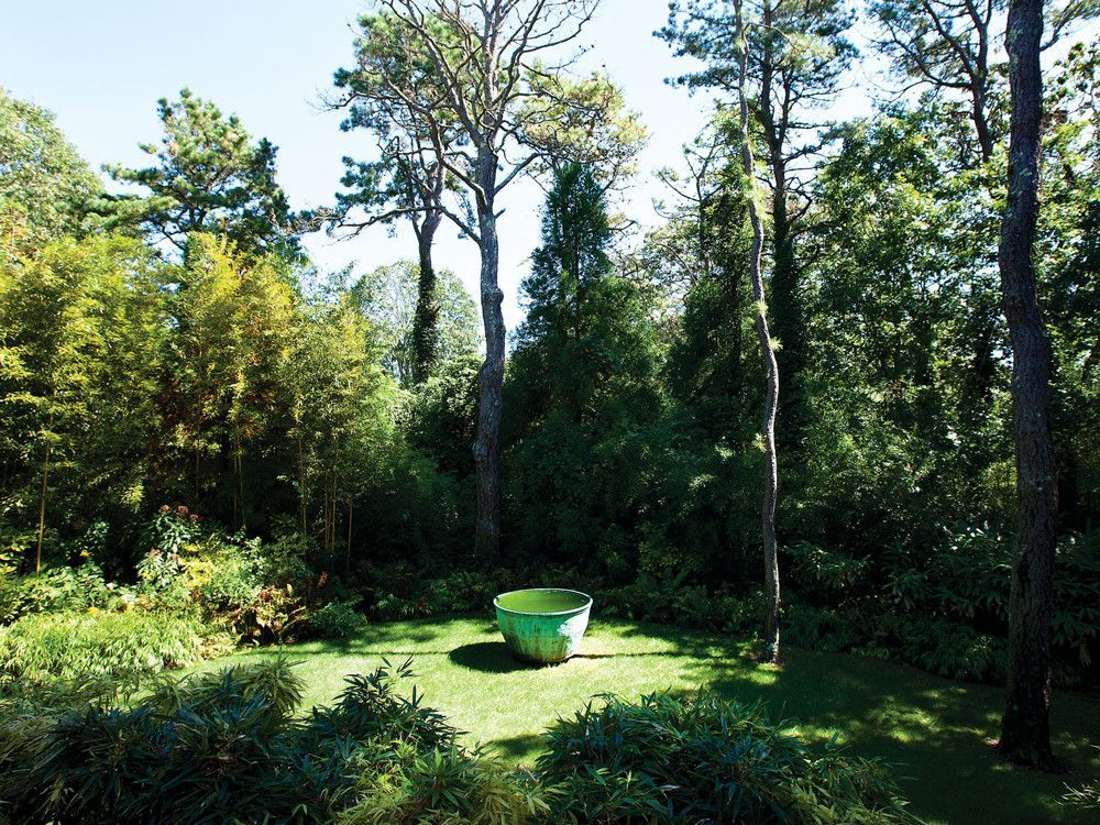 Fernandez worked with Andes Landscaping to clear overgrowth while preserving the one-acre lot's wooded maturity, enhancing it with Asian touches like the antique Taiwanese copper bath pot.