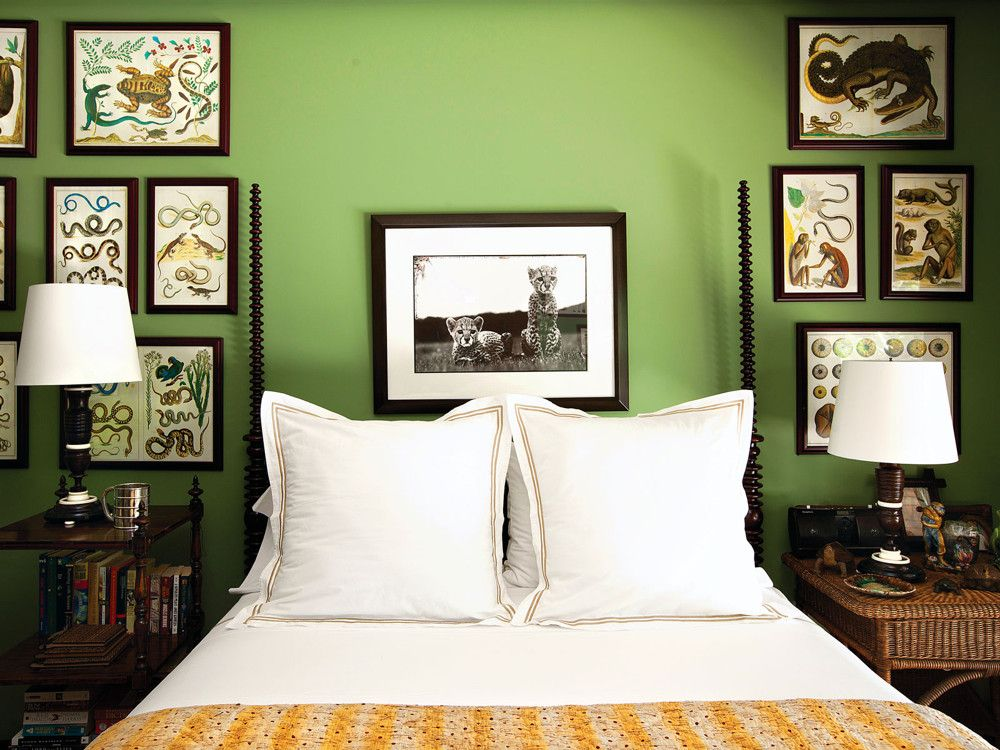 """Son Jake's green room was """"a visual response to the surroundings,"""" says Fernandez. Scientific renderings of flora and fauna, illuminated by lamps from Reborn Antiques in Los Angeles, impart an exotic colonial feel, as does the eclectic olio of a 19th-century spindle bed."""