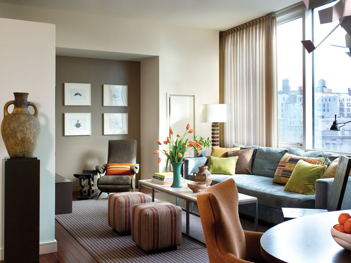 In the living room, a custom, nine-and-a-half-foot-long sofa and a lengthy coffee table take center stage over a broad-loom area rug Gissler had bound to create more visual definition. Patterned custom ottomans provide more casual seating while a sculptural Bokuro chair adds character. To take advantage of the Union Square views, the designer added lightweight but not-quite-sheer curtains. An antique olive urn from Morocco adds an artful touch.