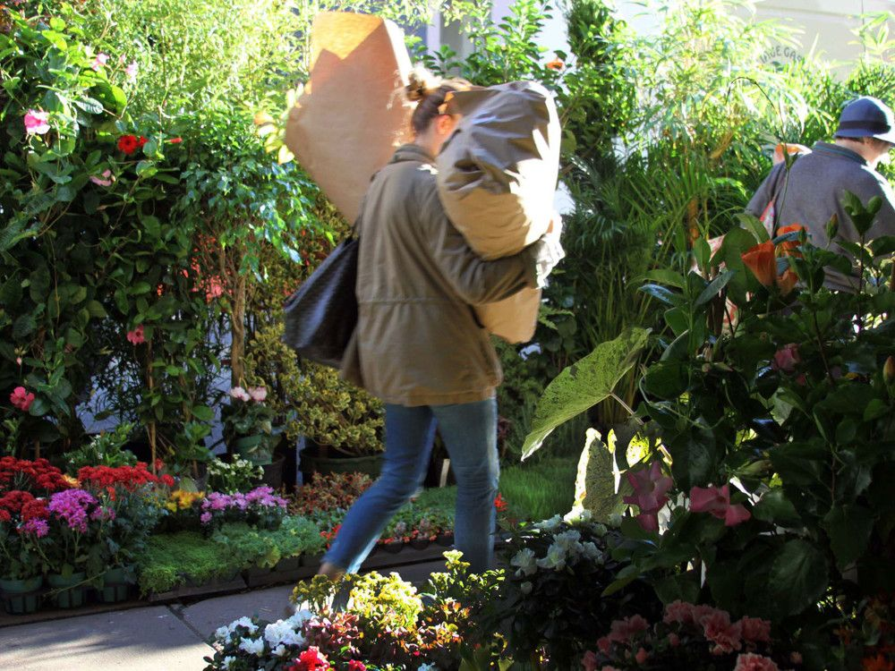 Employees and shoppers alike can be seen throughout with bundles of flowers and plants.