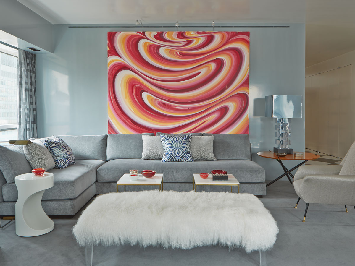 In the living room, gray is glamorous with colorful accents in the graphic pillows, red glass objets, and a curvy painting by Karin Davie. Sectional sofa from Holly Hunt is upholstered in fabric from Pollack. A white lamb bench from Mitchell Gold + Bob Williams adds a touch of glam, and a sexy side table from Holly Hunt adds sculptural interest.