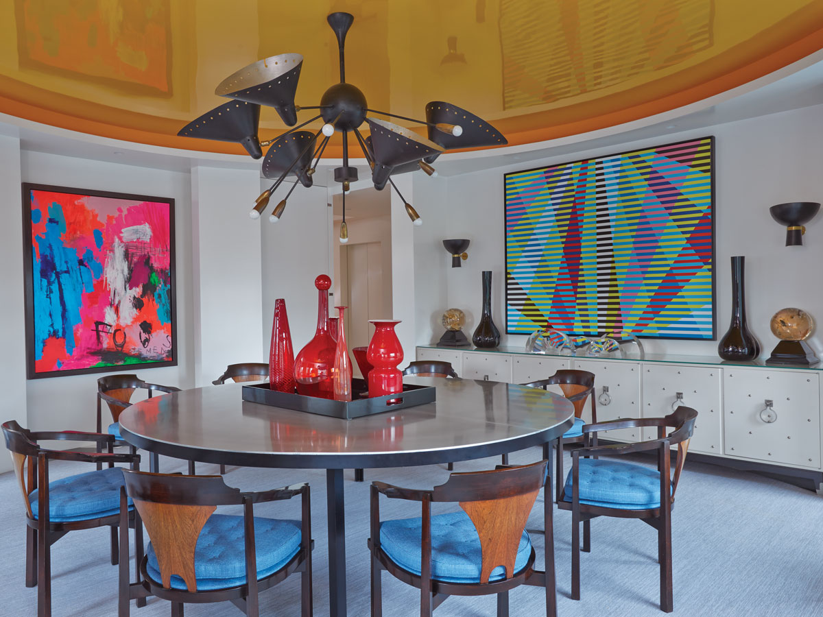 Barman created a new geometry by adding gently rounded walls and a circular ceiling to the dining room. The table, a mix of wood and metal, contrasts with the midcentury Dunbar chairs upholstered in blue Houlès fabric. Paintings by Kelly Stuart Graham (over sideboard) and Agathe de Bailliencourt add vibrant color and a modern feel.
